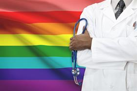 doctor standing in front of lgbtq flag